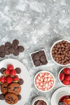 Draufsicht kekse erdbeeren und runde pralinen auf den ovalen tellerschalen mit süßigkeiten erdbeeren pralinen müsli und einer tasse tee am unteren rand des grau-weißen tisches
