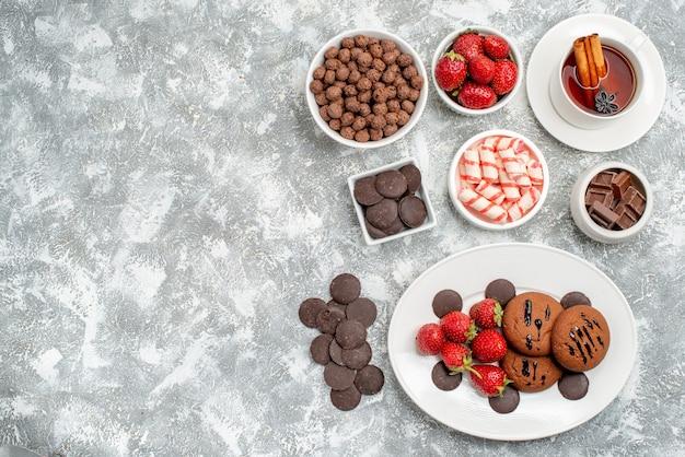 Draufsicht kekse erdbeeren und runde pralinen auf den ovalen tellerschalen mit süßigkeiten erdbeeren und pralinen müsli und eine tasse tee auf der rechten seite des grau-weißen tisches mit freiem platz