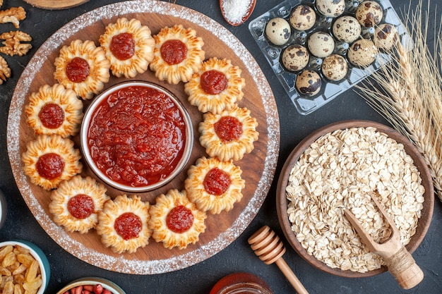 Draufsicht kekse mit marmelade und marmelade schüssel auf holzbrett hafer in schüssel weizenspitzen wachteleier in viol nüssen in schalen auf dunklem hintergrund