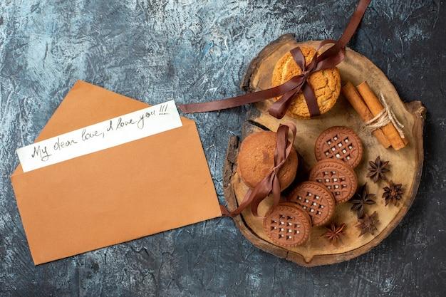 Draufsicht kekse und kekse anis zimtstangen auf holzbrett meine liebe liebe ich liebe dich geschrieben auf papierumschlag auf dunklem tisch