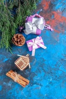 Draufsicht kiefer zweige weihnachtsbaum spielzeug weihnachtsgeschenke zimtstangen auf blau-roter oberfläche