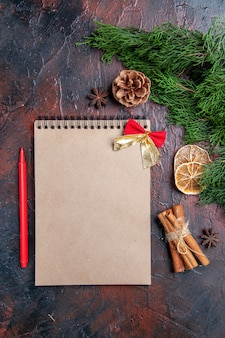 Draufsicht kiefernzweige und tannenzapfen ein notebook roter stift aniszimt auf dunkelroter oberfläche