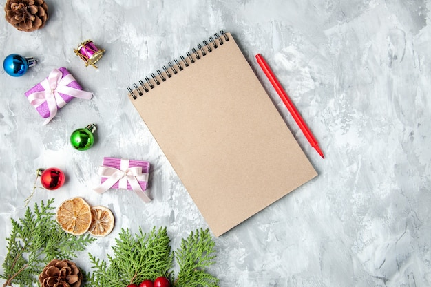 Draufsicht kieferzweige kleine geschenke weihnachtsbaum spielzeug notizbuch bleistift auf grauem hintergrund
