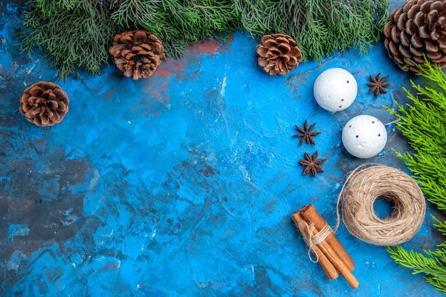 Draufsicht kieferzweige strohfaden zimtstangen anissamen weiße weihnachtsbaumkugeln auf blau-rotem hintergrund