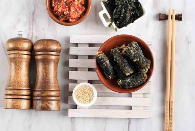 Draufsicht kimmari oder gimmari, koreanischer fried snack tempura aus algen (laver) roll gefüllt mit glasnudeln oder japchae. wird normalerweise mit tteokbokki als beilage serviert