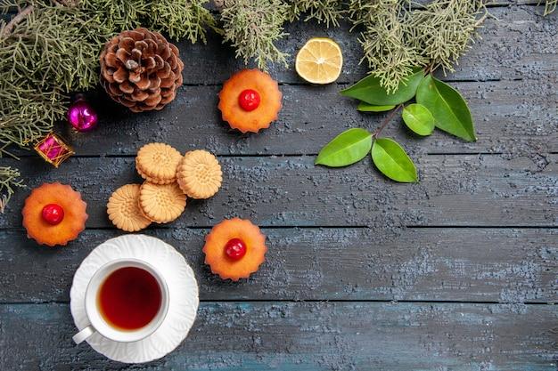 Draufsicht kirschcupcakes tannenbaumzweige zitronenscheibe eine tasse teekekse und blätter auf dunklem holztisch mit kopierraum