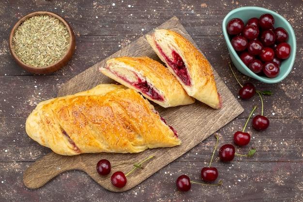 Draufsicht kirschgebäck köstlich und süß mit frischen sauerkirschen auf dem braunen hölzernen schreibtischgebäckkuchen-kekszuckersüß