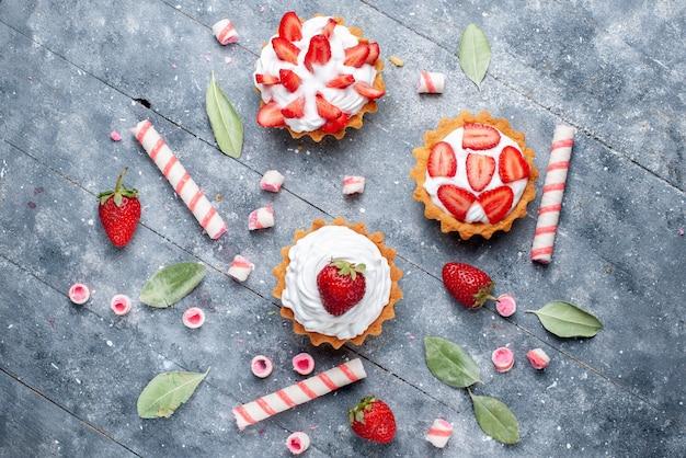 Draufsicht kleine cremige kuchen mit geschnittenen und frischen erdbeeren zusammen mit stockbonbons auf der grauen oberfläche obstkuchen süße backbeere