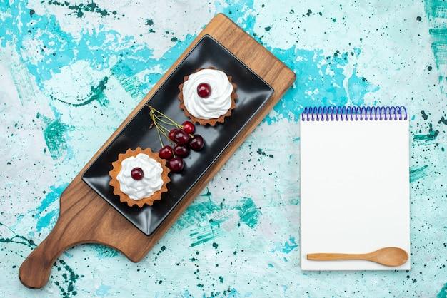 Draufsicht kleine cremige kuchen mit sauerkirschen und notizblock auf dem hellblauen hintergrundkuchenkuchen backen frucht