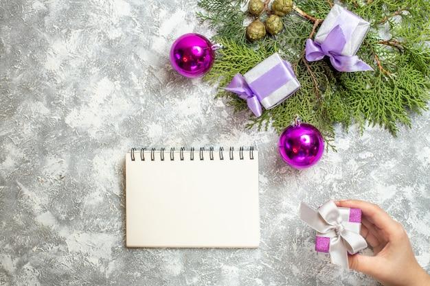 Draufsicht kleine geschenke kiefer zweige weihnachtsbaum spielzeug notebook geschenk in weiblicher hand auf grauer oberfläche