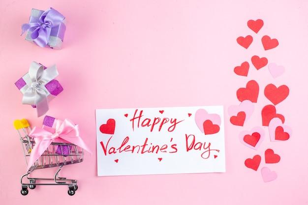 Draufsicht kleine geschenke mini-marktwagen mit geschenk happy valentinstag auf papier auf rosa hintergrund kopie platz geschrieben