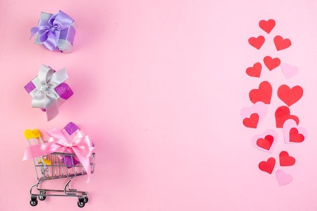 Draufsicht kleine geschenke minimarktwagen rote herzen auf rosa hintergrund freier platz