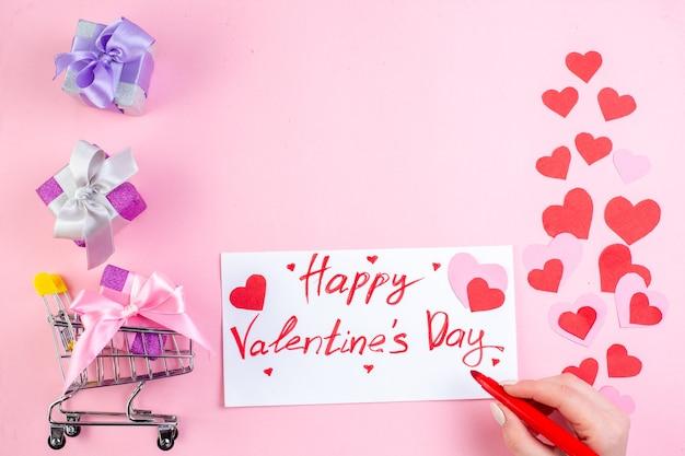 Draufsicht kleine geschenke roter marker in weiblicher hand mini-marktwagen mit geschenk happy valentinstag auf papier auf rosa hintergrund geschrieben