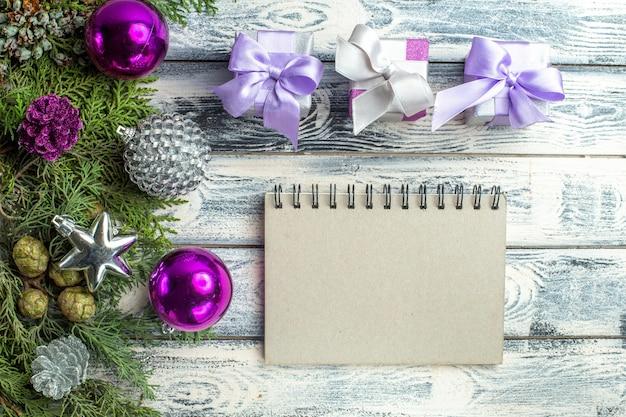 Draufsicht kleine geschenke weihnachtsbaum spielzeug tannenbaum zweige notebook auf holzuntergrund