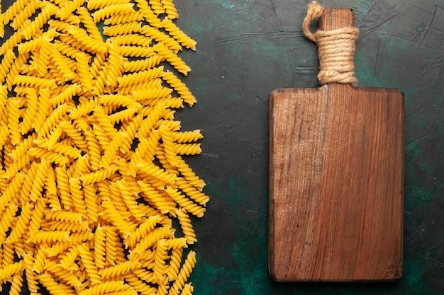 Draufsicht kleine italienische nudeln mit hölzernem schreibtisch auf dunklem hintergrundnahrungsmittelmahlzeit-rohem italien-teig