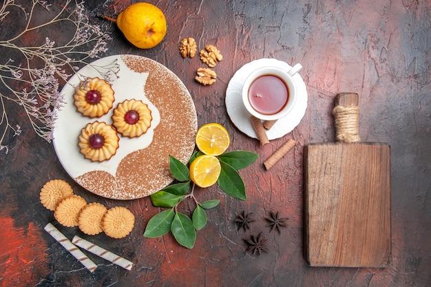 Draufsicht kleine kekse mit tasse tee auf dunklem tischzucker-kekskuchen süß