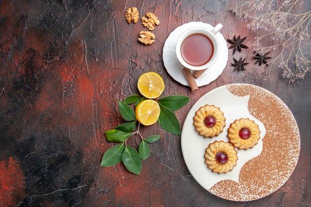 Draufsicht kleine kekse mit tasse tee auf dunklem tischzuckerplätzchenkuchen süß