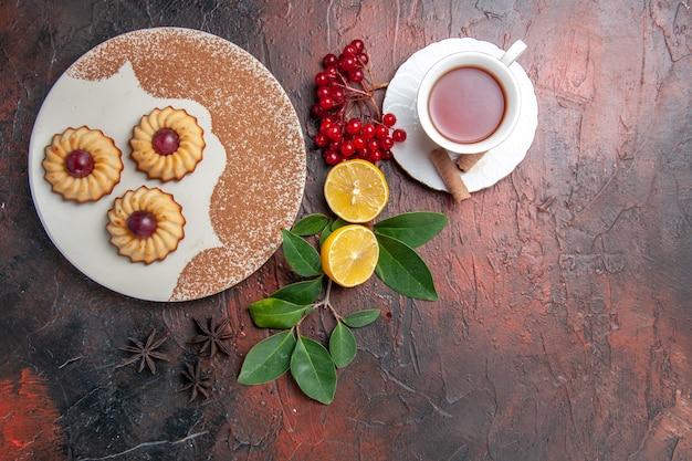 Draufsicht kleine kekse mit tee auf dunklem tischkekskuchen süß