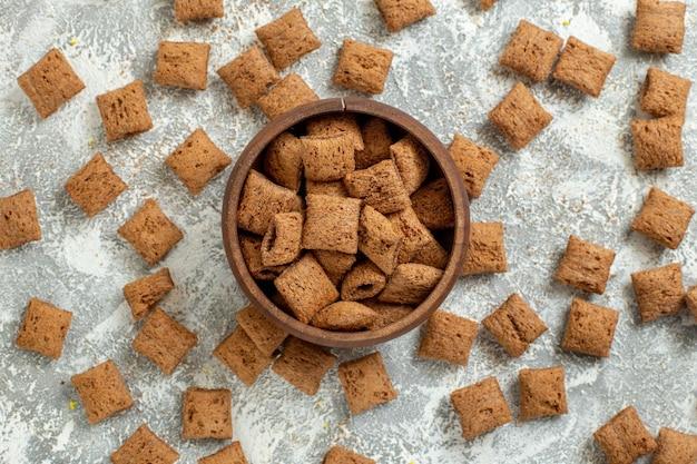 Draufsicht kleine kissenflocken süße kekse auf weißer oberflächenfarbe mahlzeit frühstücksmilch