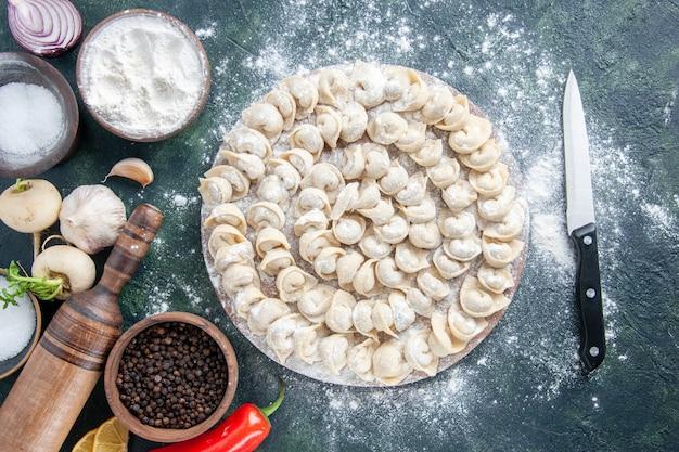 Draufsicht kleine knödel mit mehl und gemüse auf dunklem hintergrund fleischteig lebensmittelteller farbe gemüsemehl