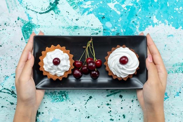 Draufsicht kleine köstliche kuchen mit sahne und früchten auf dem hellblauen tischkuchen süße sahnefrucht