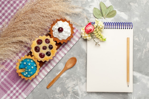 Draufsicht kleine köstliche kuchen mit sahne und früchten notizblock auf dem hellen hintergrundkuchen süße sahne backen fruchtfoto