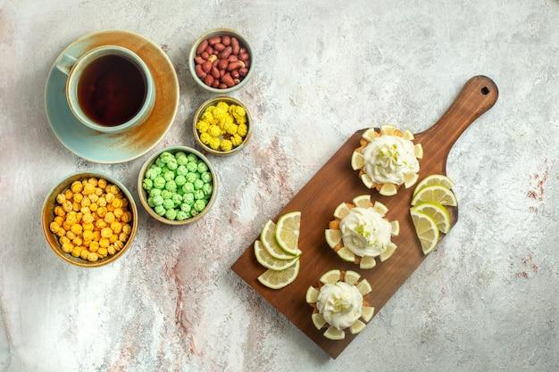 Draufsicht kleine köstliche kuchen mit tasse tee und bonbons auf weißer oberfläche kuchenkeksplätzchen süße teecreme