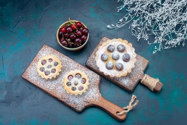 Draufsicht kleine köstliche kuchen zucker pulverisiert mit sauerkirschen auf dem dunklen hintergrund kuchen zucker süße backfarbe