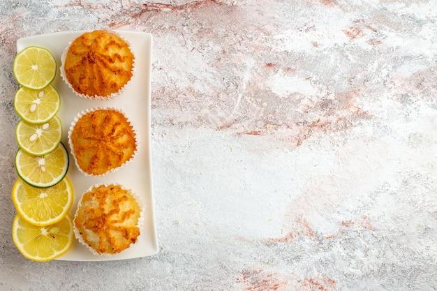 Draufsicht kleine kuchen gebacken und mit zitronenscheiben auf weißer oberfläche