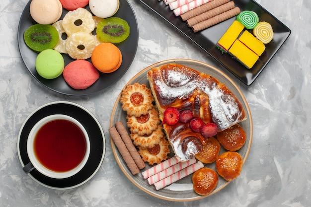 Draufsicht kleine kuchen mit keksen tasse tee und torte auf weißem backgruond-kekskeks süßer zuckertorte tee