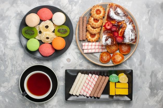 Draufsicht kleine kuchen mit kekstasse tee und dessert auf weißem backgruond-kekskeks süßer zuckerkuchen-tee