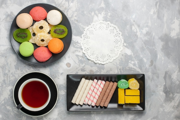 Draufsicht kleine kuchen mit kekstasse tee und kekse auf weißem backgruond-kekskeks süßer zuckertorten-tee