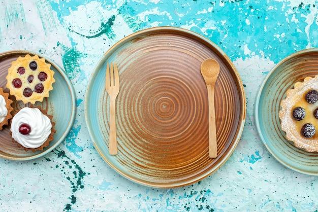 Draufsicht kleine kuchen mit sahne auf dem hellblauen hintergrundkuchen süßer auflauf auf dem hellen hintergrundkuchen sahnezucker süßer auflauf