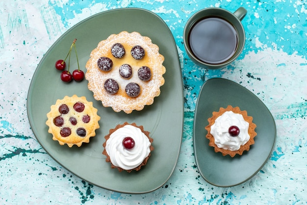 Draufsicht kleine kuchen mit tee auf dem hellblauen tischkuchenkuchen kirschfrucht süß