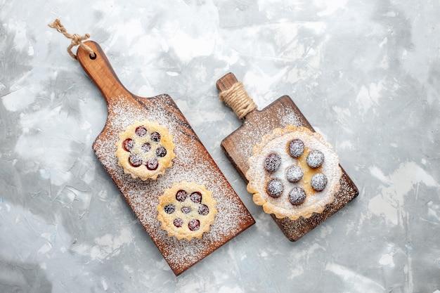 Draufsicht kleine kuchen mit zuckerpulver und früchten auf dem süßen farbfoto des leichten schreibtischkuchenkekszuckers