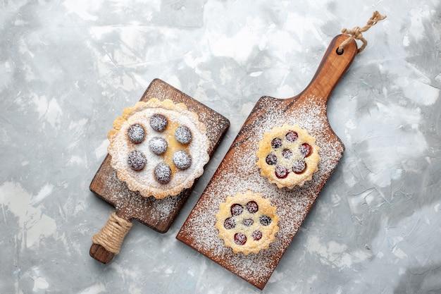 Draufsicht kleine kuchen zucker pulverisiert mit früchten auf dem leichten schreibtisch obstkekskuchen süßer zucker