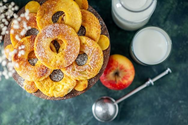 Draufsicht kleine leckere kuchen in ananasringform mit milch auf dunkelblauem hintergrund obstkuchen gebäck kuchen hotcake farbe backen