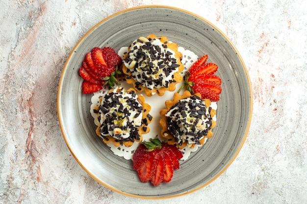 Draufsicht kleine leckere kuchen mit sahne und erdbeeren auf weißer oberfläche geburtstagsfeier kuchen süßer keks