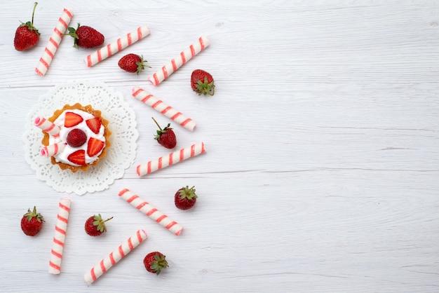 Draufsicht kleine leckere kuchen mit sahne und geschnittenen erdbeersüßigkeiten auf dem weißen hintergrundkuchenbeeren-süßen auflauf