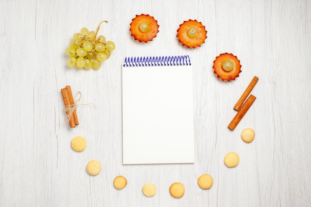 Draufsicht kleine leckere kuchen mit trauben-notizblock und keksen auf weißem schreibtisch obstkuchen keks süßer desserttee