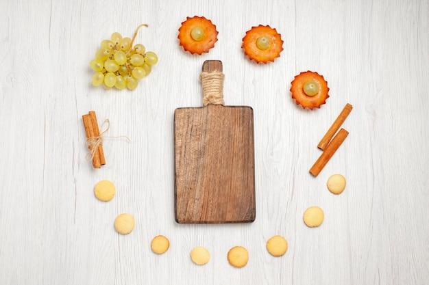Draufsicht kleine leckere kuchen mit trauben und keksen auf dem weißen schreibtisch obstkuchen keks süßer desserttee