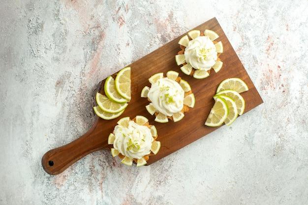 Draufsicht kleine leckere kuchen mit zitronenscheiben auf weißer oberfläche kuchen keks keks süßer tee sahne zucker