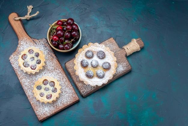 Draufsicht kleine leckere kuchen mit zuckerpulverfrüchten zusammen mit frischen sauerkirschen auf dem dunklen hintergrundkuchenkekszuckersüßbacken