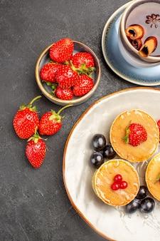 Draufsicht kleine leckere pfannkuchen mit früchten und tasse tee auf grauem schreibtischkuchenkuchenfrucht