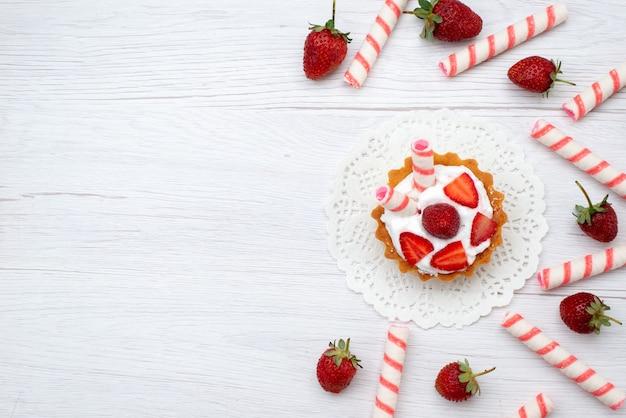 Draufsicht kleine leckere torte mit sahne und geschnittenen erdbeeren kleben bonbons auf den weißen hintergrund kuchen beere süßen zucker backen