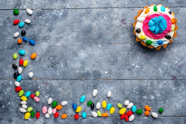 Draufsicht kleine leckere torte mit sahne und verschiedenen bunten bonbons überall auf dem licht schreibtisch süßigkeit süßer zucker farbkuchen foto