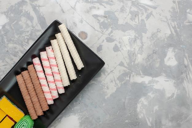 Draufsicht kleine pfeifenkekse mit marmelade auf hellweißem hintergrundplätzchenkekszuckerkuchenkuchen