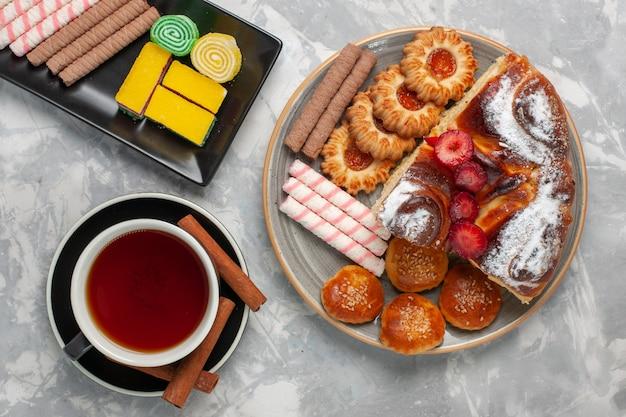 Draufsicht kleine pfeifenkekse mit marmeladentasse tee und kleinen kuchen auf weißem hintergrundplätzchenkekszuckerkuchen