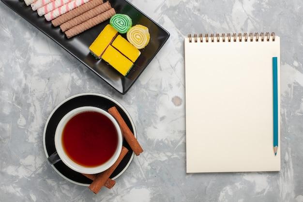 Draufsicht kleine pfeifenplätzchen mit marmelade und tasse tee auf weißem hintergrundplätzchenkekszuckerkuchen