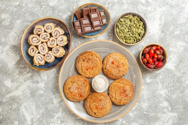 Draufsicht kleine rollbonbons mit keksen auf weißem hintergrund